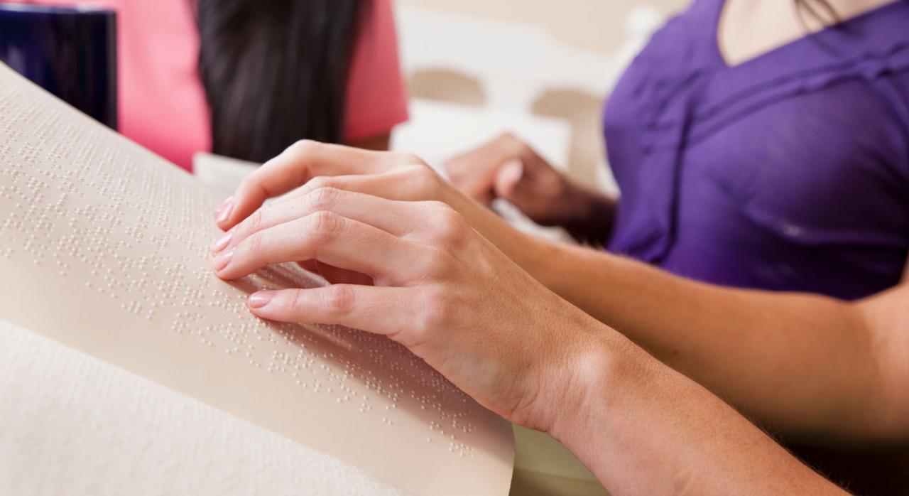 ONCE. Gran invalidez. Persona leyendo un libro en braille