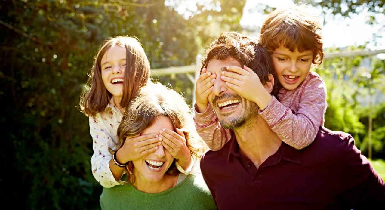 Complemento género. Dos niños subido a la espalda de su madre y su padre respectivamente y les tapan los ojos con las manos
