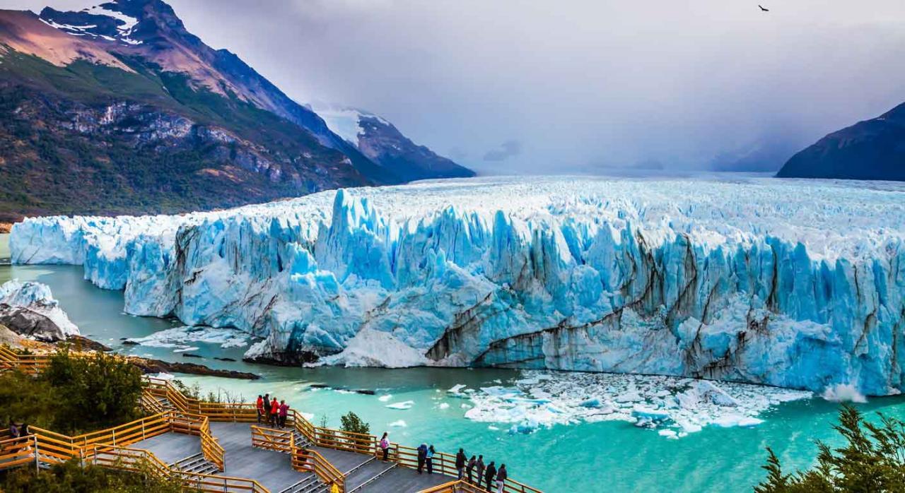 Jurisprudencia. Gente asomada a una barandilla observando un glaciar, las montañas y un río