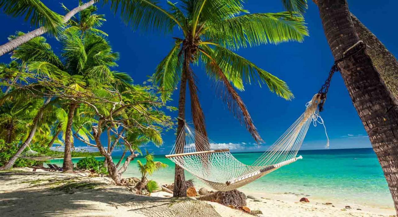 Trabajo a tiempo parcial; Ampliaciones de jornada; Vacaciones. Una hamaca atada a unas palmeras en una playa vacia