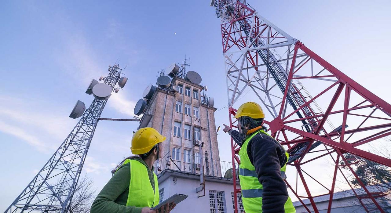 Periodo de guardia; disponibilidad no presencial; tiempo de trabajo. Imagen de ingenieros trabajando cerca de una torre de telecomunicaciones