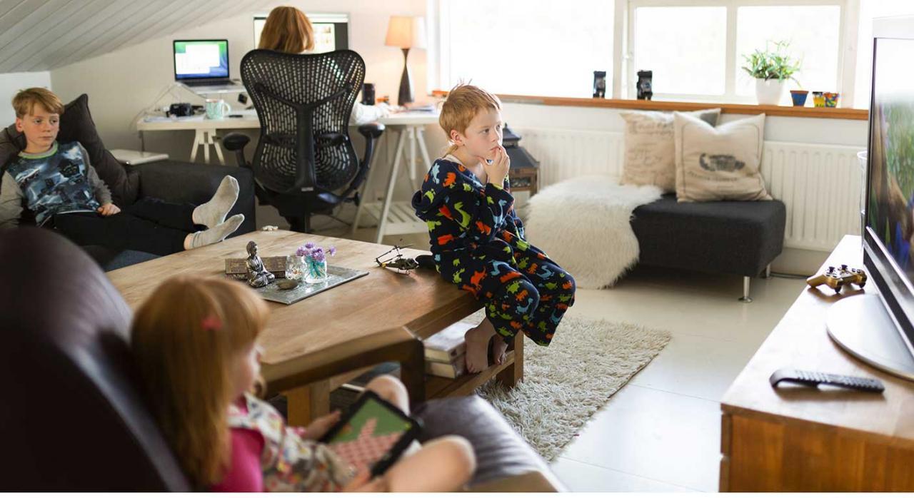 Permiso obligatorio, retribuido y recuperable. Imagen de una señora teletrabajando con sus hijos en el salón