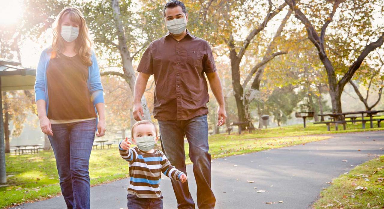 Permiso parental; nacimiento; adopción. Imagen de unos padres paseando con su hijo