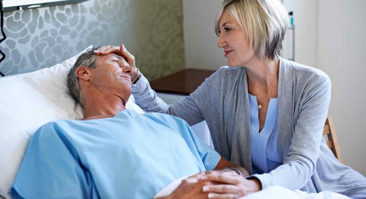 Intervención quirúrgica sin hospitalización. Hombre en la cama de un hospital acompañado de su mujer
