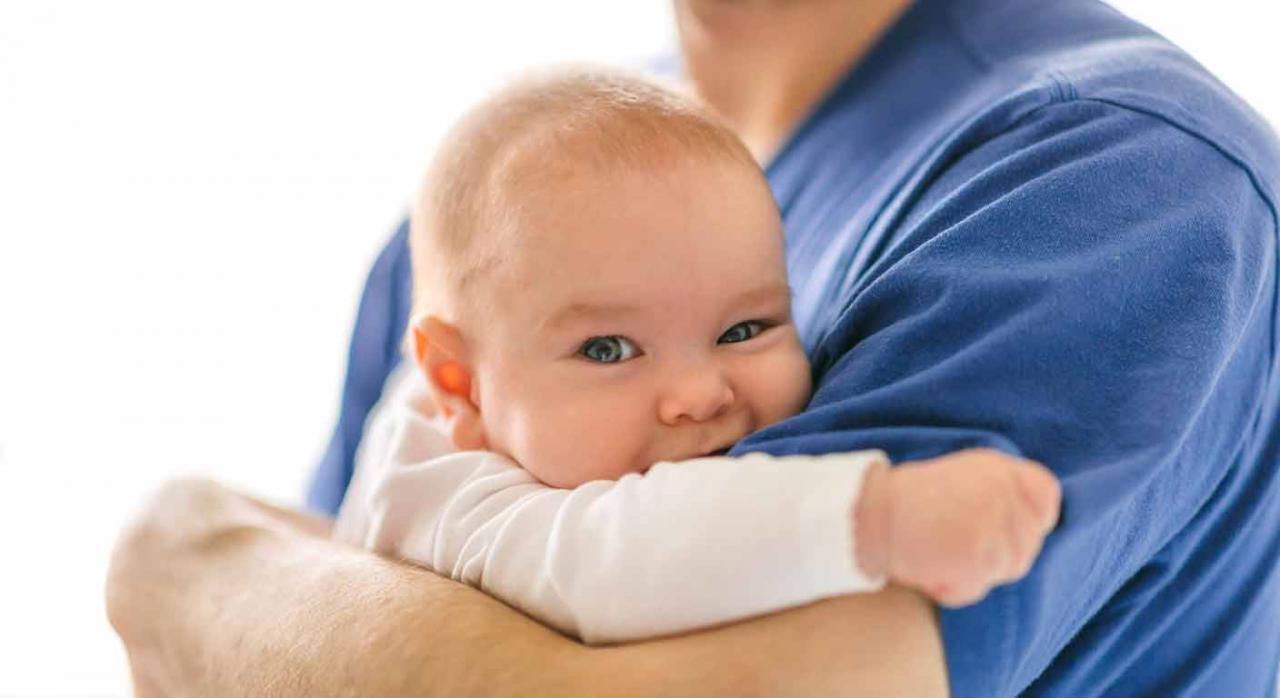 Permiso retribuido por paternidad. Padre sosteniendo en brazos a un bebé