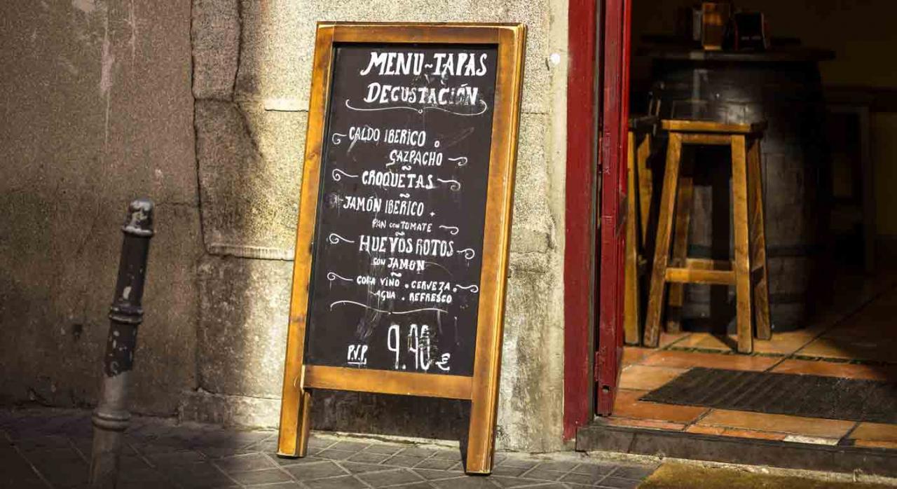 ERTE; fuerza mayor temporal; resolución administrativa; notificación. Pizarra en la puerta de un bar con el menú y tapas escritos