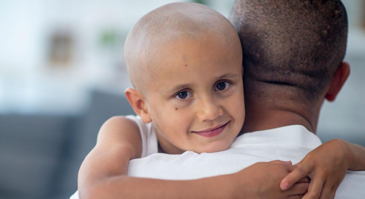 TSJ. Prestación por cuidado de hijo menor afectado por cáncer u otra enfermedad grave cuyo beneficiario es el padre. No se suspende en caso de nacimiento de un nuevo hijo durante el periodo de descanso por maternidad del otro progenitor. Imagen de un niño enfermo abrazando a su padre