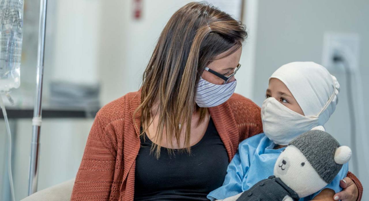 El acceso a la prestación está condicionado a que ambos progenitores trabajen, sin excepciones. Imagen de madre con bebé en brazos en un entorno hospitalario y ambos con mascarilla