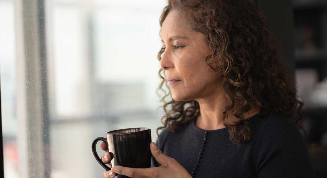 Prestación en favor de familiares. Mujer con una taza en la mano mirando a través de la ventana