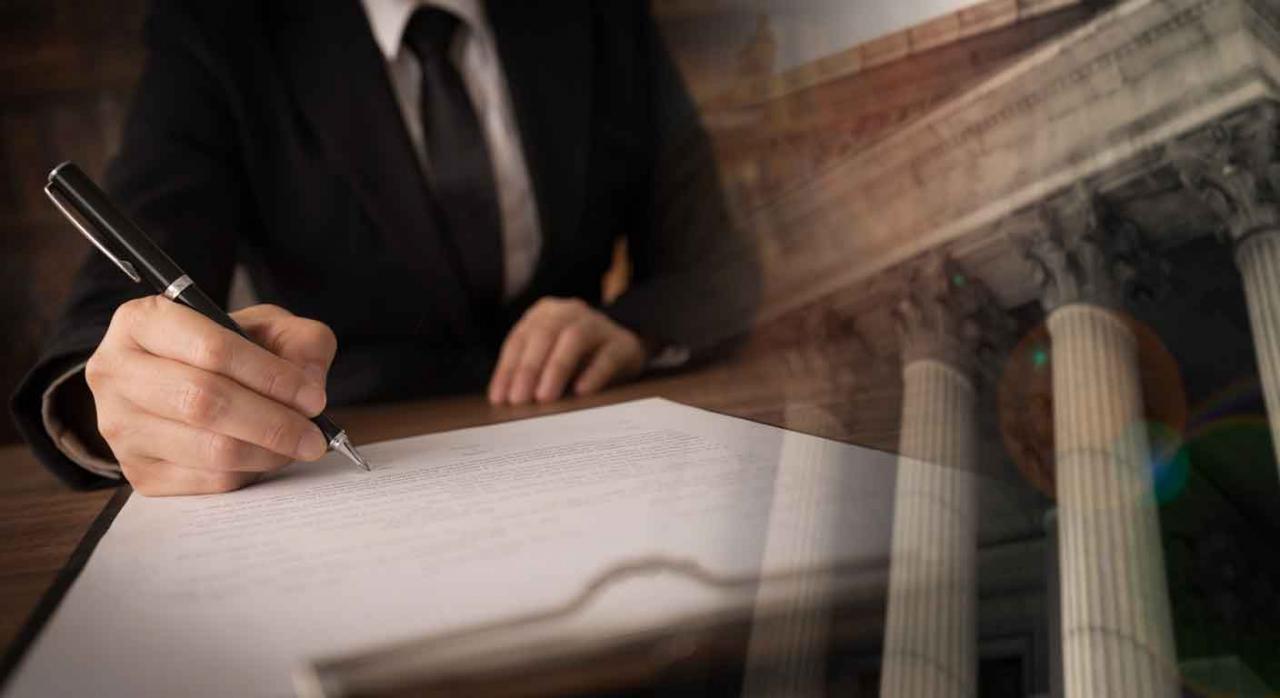 Imagen de un señor firmando un papel como en un juzgado
