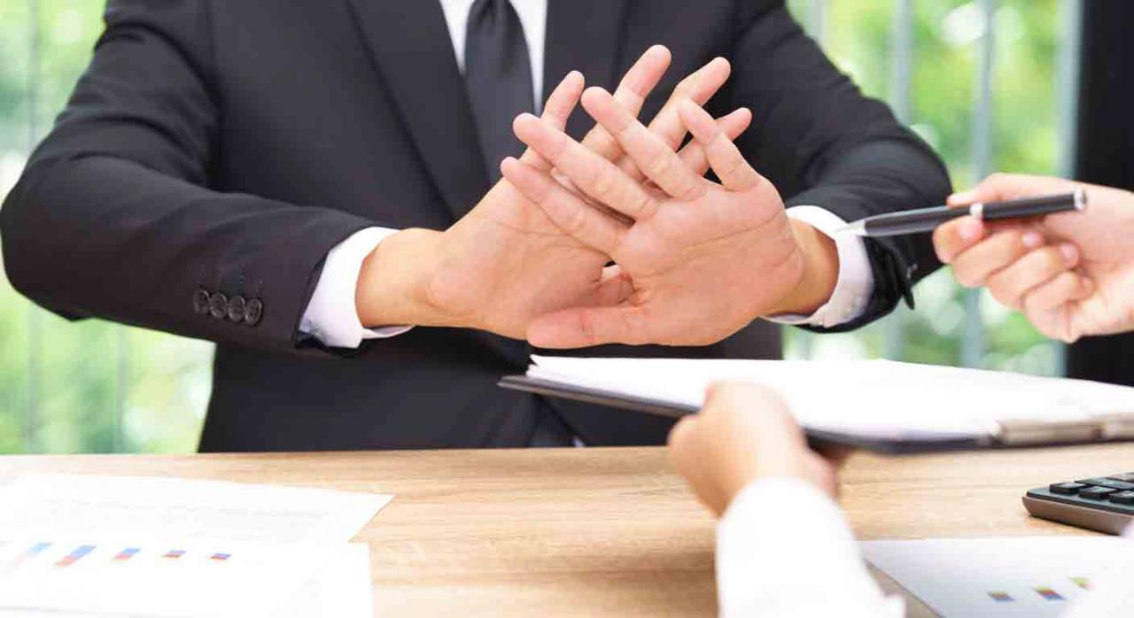 Problemas en la empresa por el despido de un empleado. Empleado negando con las manos firmar unos documentos