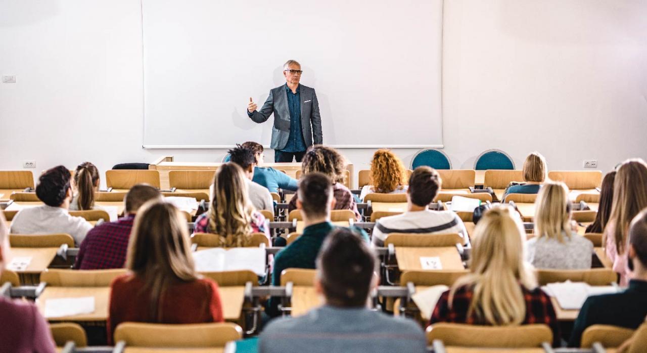 Profesor hablando con un grupo de estudiantes universitarios en un anfiteatro