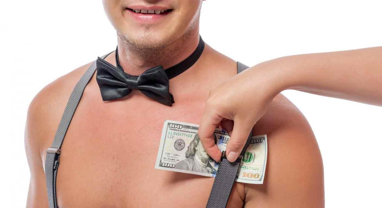 Prostitución voluntaria por cuenta ajena. Mano femenina pone dólares debajo del tirante de un hombre desnudo
