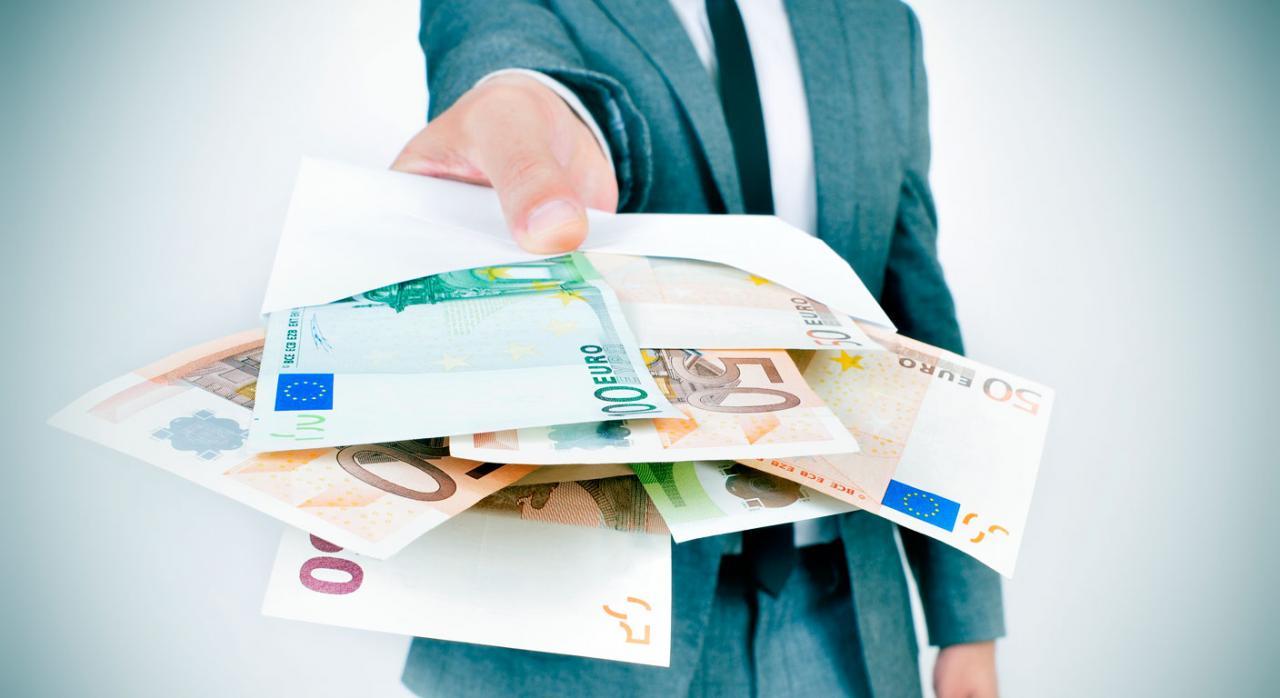 Hombre dando un sobre lleno de billetes de euro. Prestaciones indebidas