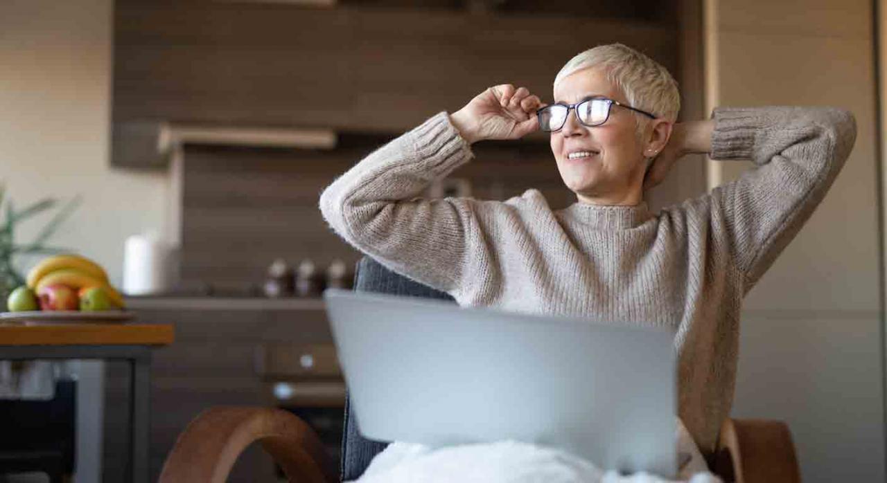 Renta activa de inserción. Mujer sentada en un sillon con un portátil en sus rodillas