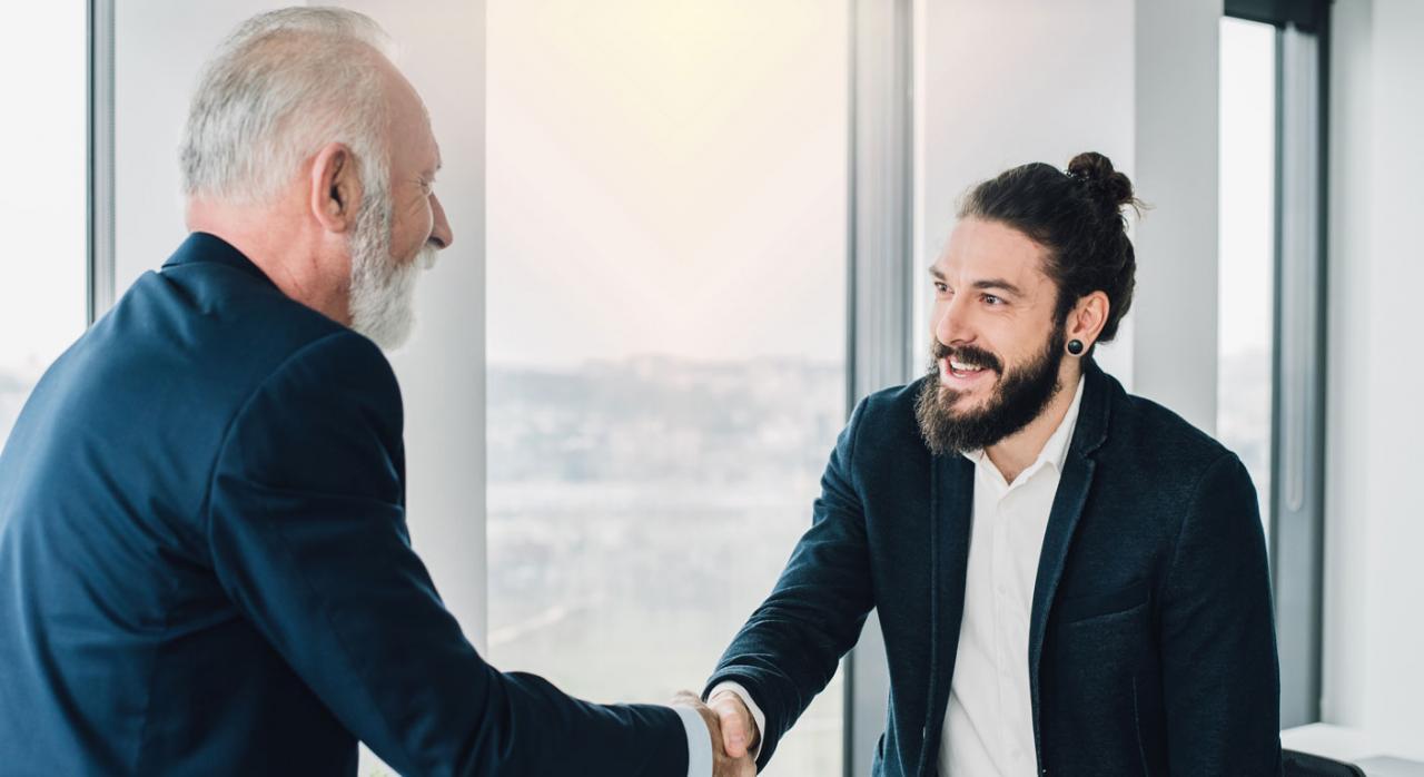 Compañeros de trabajo de diferentes edades estrechándose la mano en la oficina