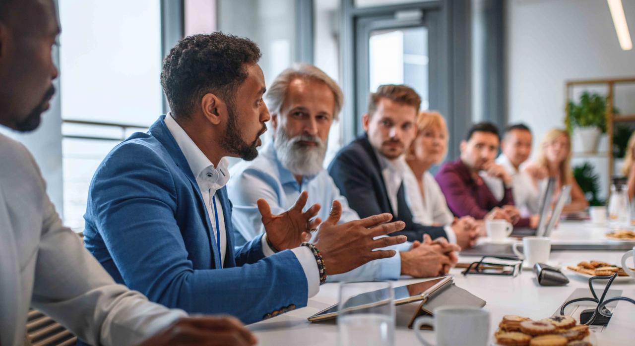 Convenios colectivos; comisión paritaria. Reunión de trabajo, un hombre hablando y los demás escuchando atentamente