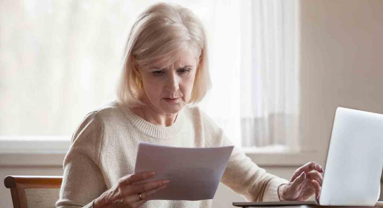 Pensiones concurrentes; complemento por mínimos. Señora sentada delante de un ordenador mirando con atención unos papeles