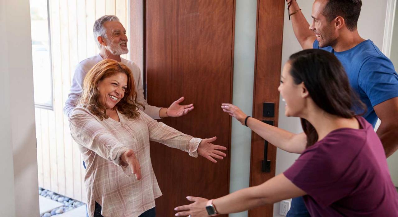 Socios trabajadores de cooperativas de trabajo asociado. Pareja jóven recibiendo en la puerta de su casa a otra pareja más mayor