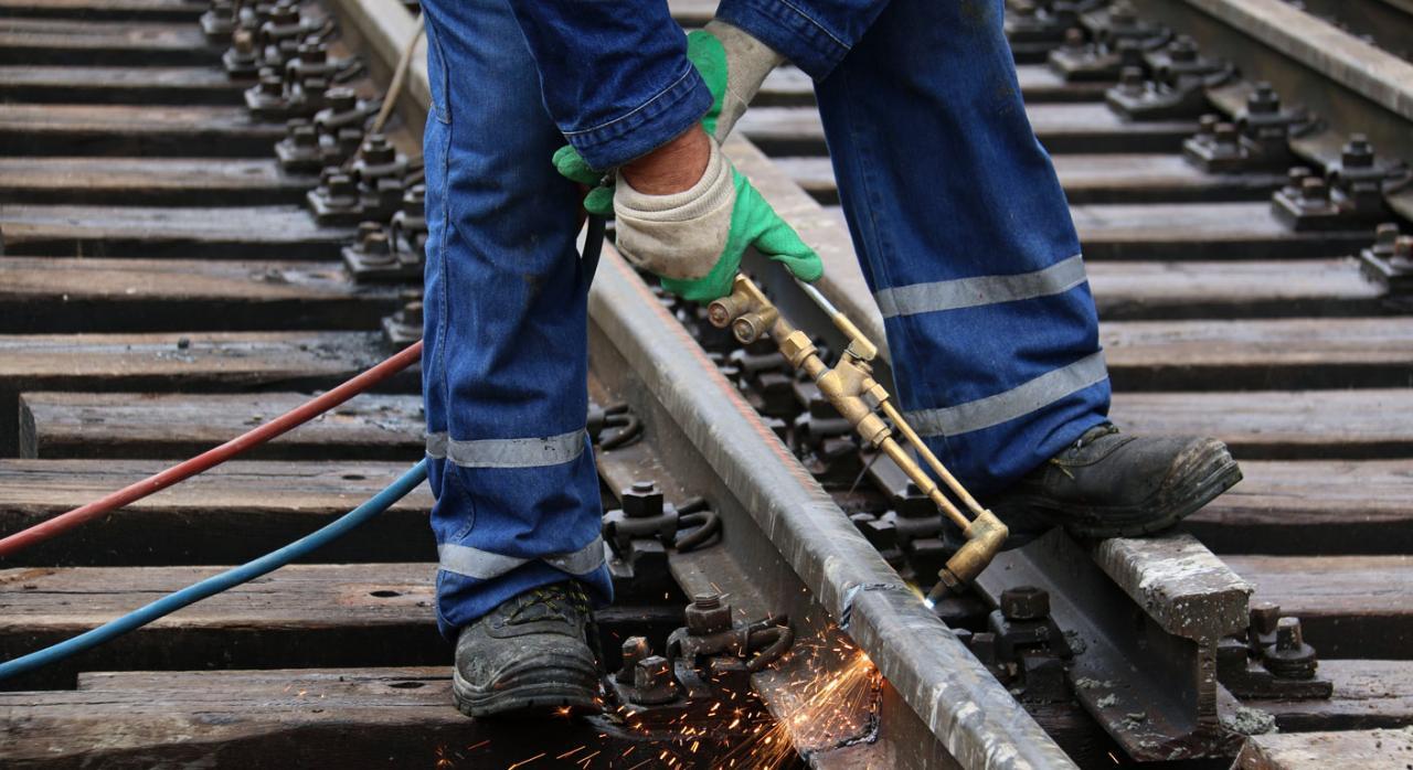 Trabajador soldando en una vía de tren. Sucesión de empresa