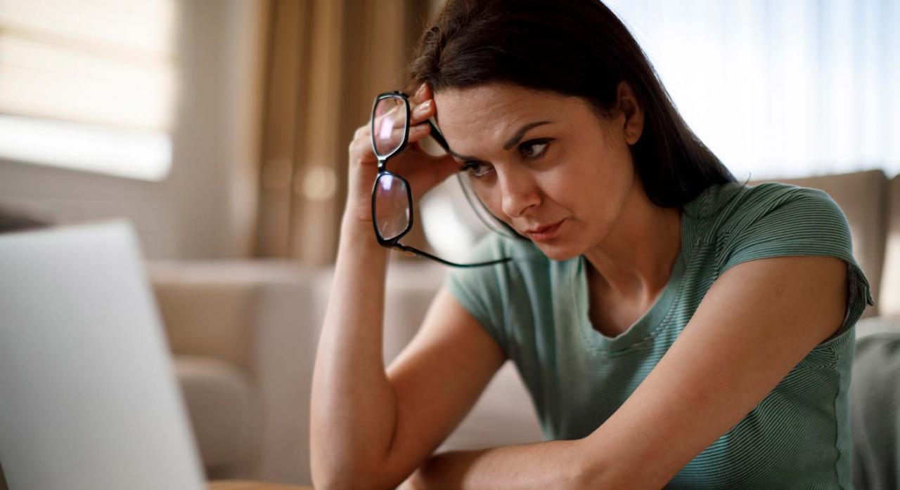 El art. 41 del ET no permite de forma indiscriminada que el empleador modifique condiciones colectivas. Imagen de mujer sentada frente al ordenador pensativa