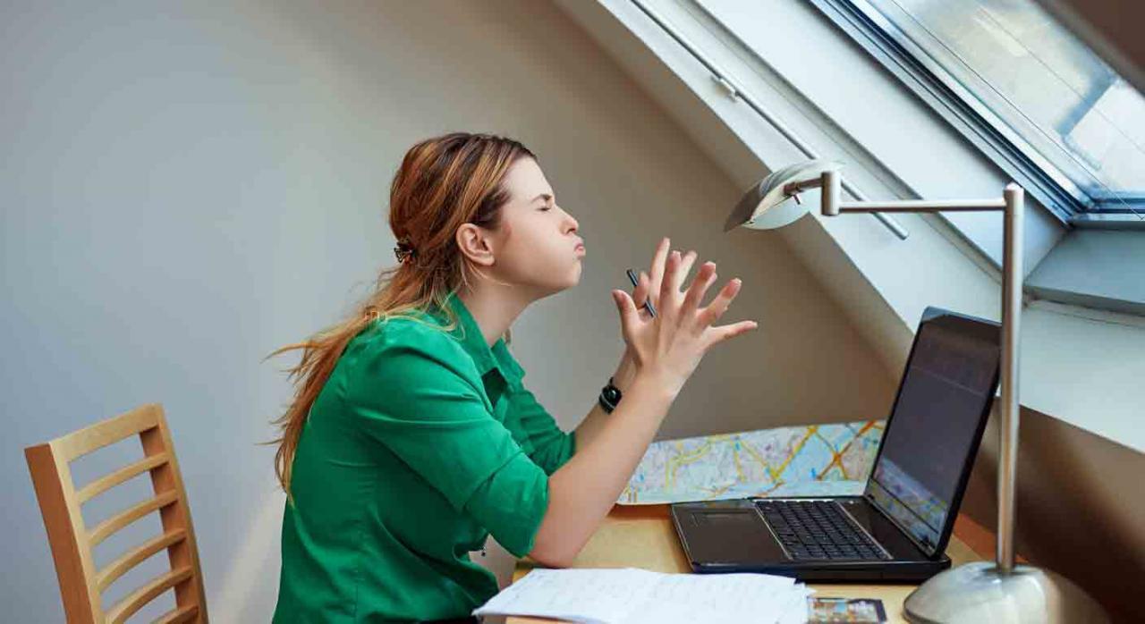 Desconexiones que impidan la prestación del teletrabajo. Mujer delante del portátil con gesto de enfado