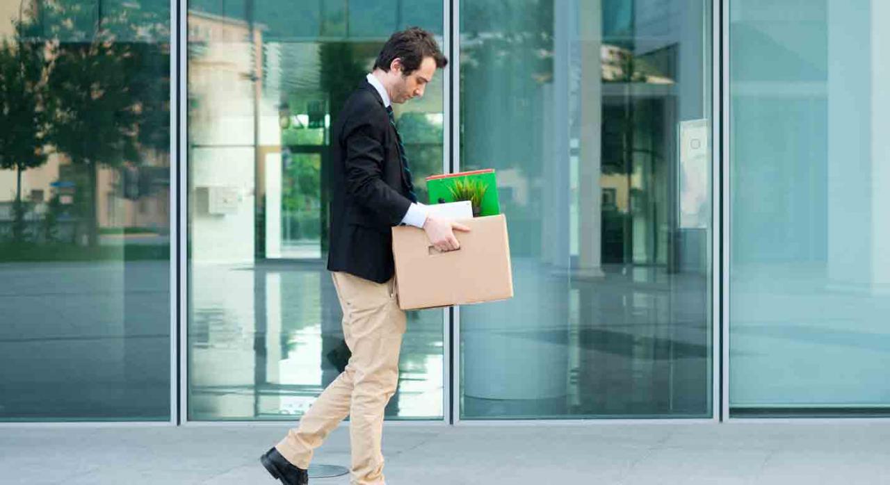 Despido; comunicación; fecha de efectos. Trabajador despedido andando sujetando una caja con sus pertenencias