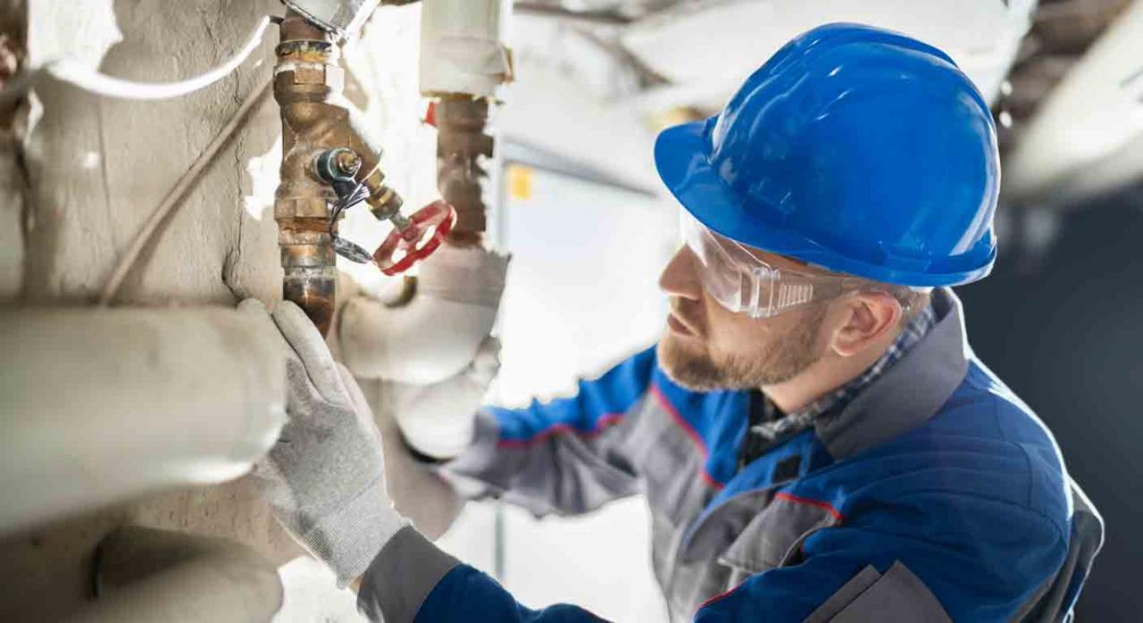 Contrato de obra; duración; contratas y subcontratas. Trabajador revisando una válvula en una instalación