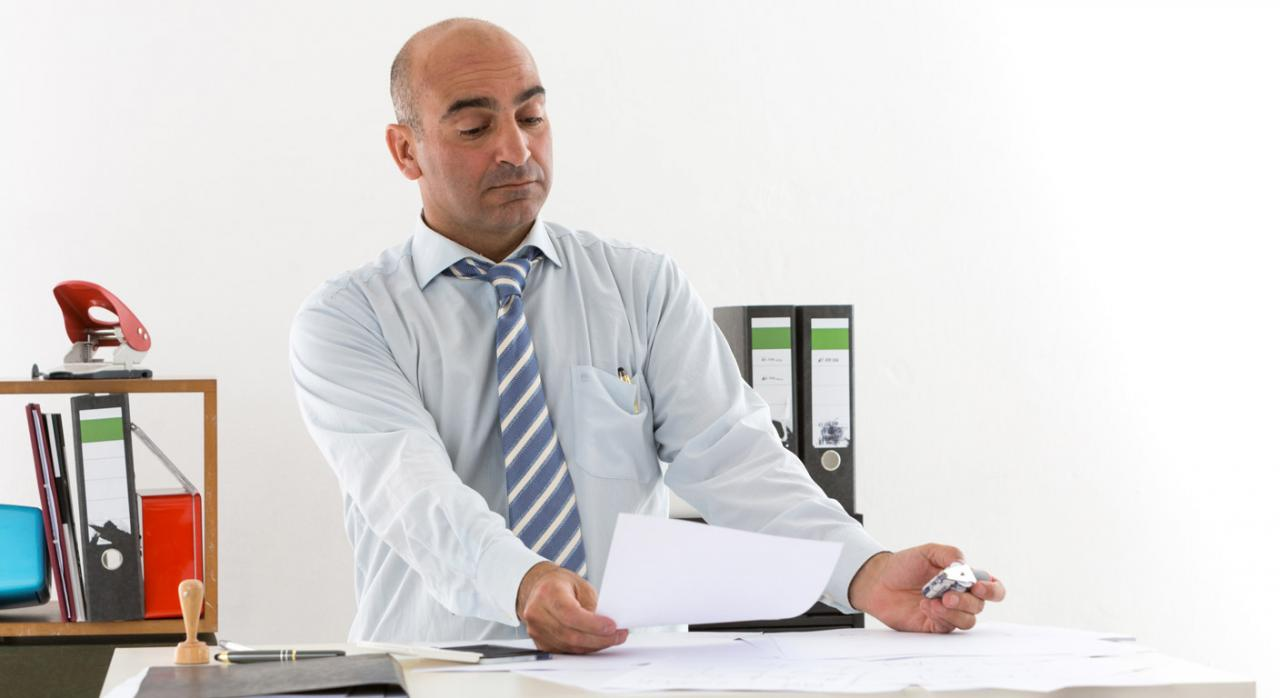 Trabajador alejando los papeles para ver bien