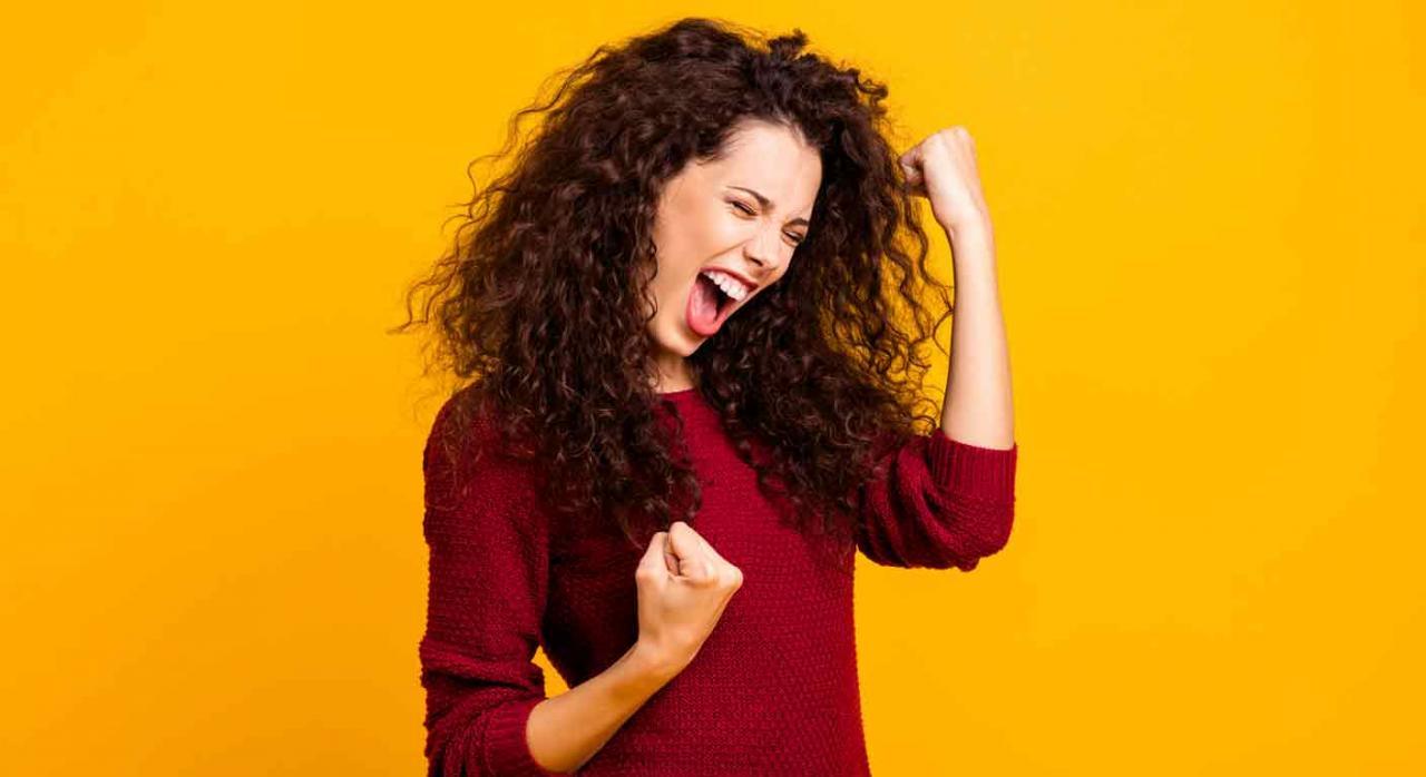 Mujer gritando con los puños en alto con expresión de alegría. Trienios por trabajadores fijos discontinuos