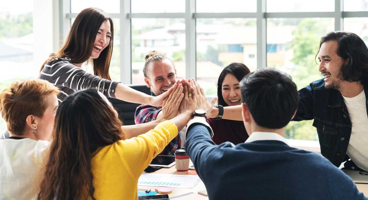 Trabajadores motivados. Imagen de un grupo de trabajadores multiétnico chocando manos y riendo en reunión brainstorm en oficina