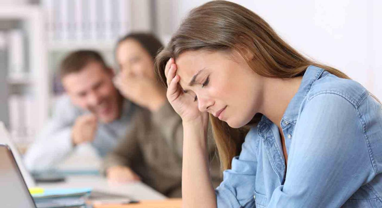 Detectar trabajores tóxicos y recompensar profesionales. Trabajadora sufriendo las burlas de sus compañeros