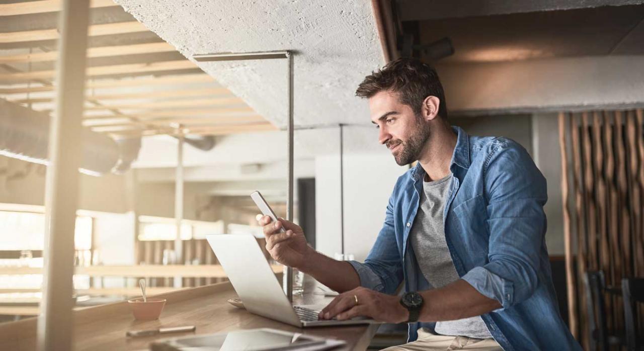 Utilización de las apps en las empresas. Hombre en un cafetería frente a un portátil y un móvi