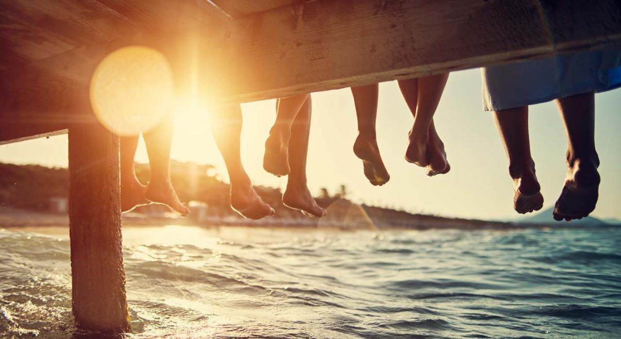 Las vacaciones mejoran la productividad. Personas sentadas sobre un muelle en el mar