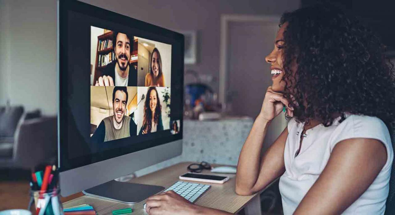 Buena gestión de RRHH. Una chica sonriente mantiene una videollamada con cuatro amigos desde el ordenador de su casa