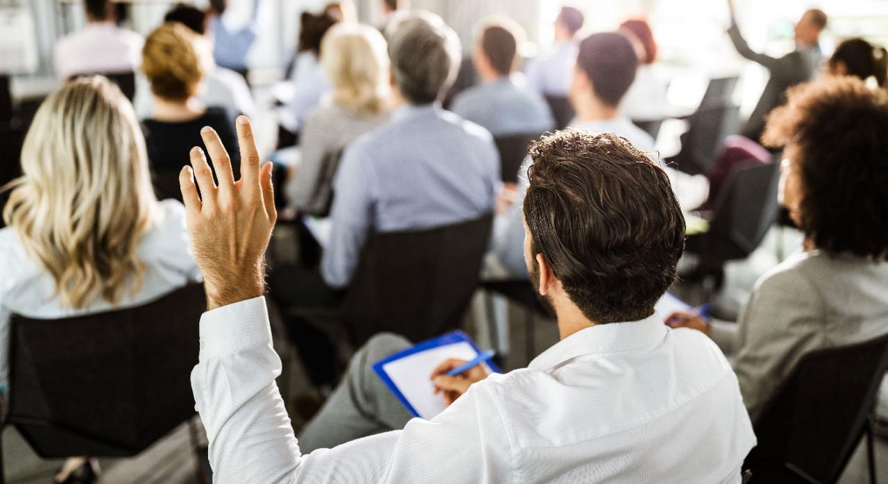 Empresario levantando la mano en un seminario para preguntar