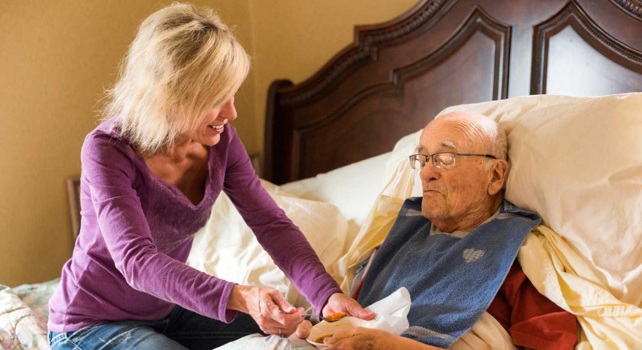 Pensión de viudedad. Mujer ofreciendo cuidados a un hombre postrado en cama