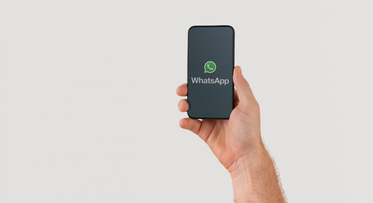 Imagen de mano sujetando un teléfono inteligente con el logotipo de WhatsAppup